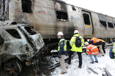 """NTSB investigators survey the vehicles involved in a Metro North accident at Valhalla, N.Y. (""""Metro North accident at Valhalla, NY - 1"""" by National Transportation Safety Board - https://www.flickr.com/photos/ntsb/15824330913/in/set-72157650647203205. Licensed under Public Domain via Wikimedia Commons - https://commons.wikimedia.org/wiki/File:Metro_North_accident_at_Valhalla,_NY_-_1.jpg#/media/File:Metro_North_accident_at_Valhalla,_NY_-_1.jpg)"""