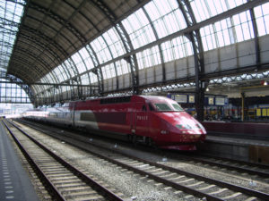 """(""""Thalys Amsterdam Centraal"""". Licensed under Public Domain via Wikimedia Commons - https://commons.wikimedia.org/wiki/File:Thalys_Amsterdam_Centraal.jpg#/media/File:Thalys_Amsterdam_Centraal.jpg)"""